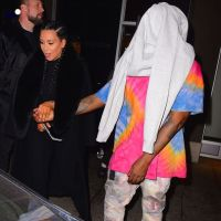 Kim Kardashian shows off her post baby body as Kanye bizarrely covers up his face (Photos)