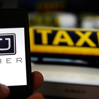 File illustration picture showing the logo of car-sharing service app Uber on a smartphone next to the picture of an official German taxi sign in Frankfurt, September 15, 2014. A Frankfurt court earlier this month instituted a temporary injunction against Uber from offering car-sharing services across Germany. San Francisco-based Uber, which allows users to summon taxi-like services on their smartphones, offers two main services, Uber, its classic low-cost, limousine pick-up service, and Uberpop, a newer ride-sharing service, which connects private drivers to passengers - an established practice in Germany that nonetheless operates in a legal grey area of rules governing commercial transportation.    REUTERS/Kai Pfaffenbach/Files  (GERMANY - Tags: BUSINESS EMPLOYMENT CRIME LAW TRANSPORT)