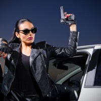 Young gangster woman with gun near the car