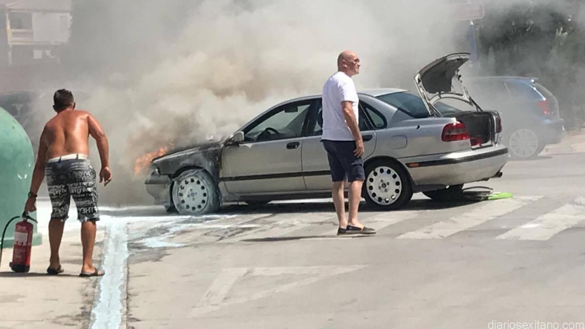 Vecinos, policia y bomberos tratan de sofocar el incendio de un vehículo en La Herradura