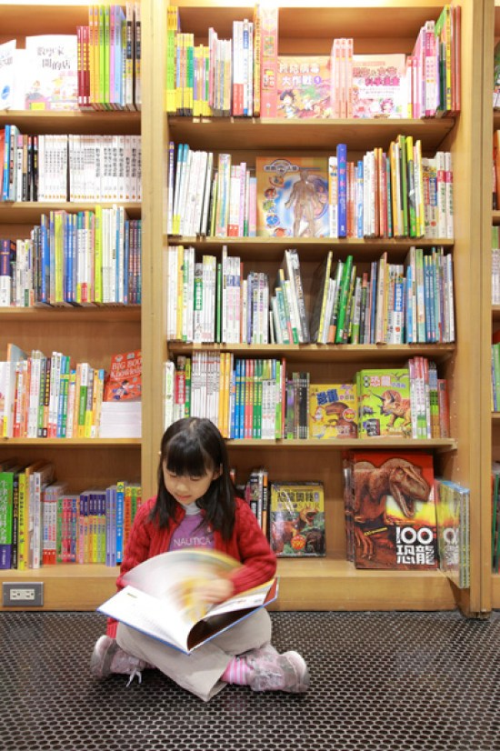A little Chinese girl reading a book inside a bookstore.