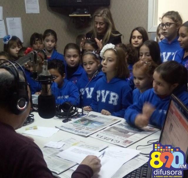 Na foto, alunos conhecem o estúdio da emissora, com o locutor Vanderlei Santos