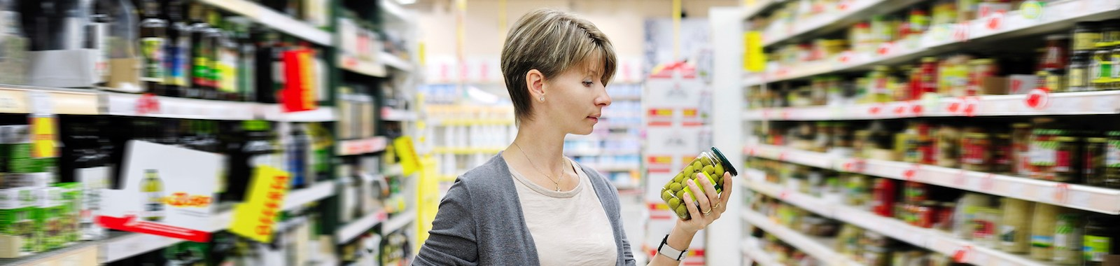 woman shopping and choosing goods at supermarket