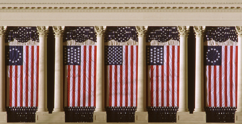 The U.S. Capitol is draped with two versions of the flag during the Inauguration period.