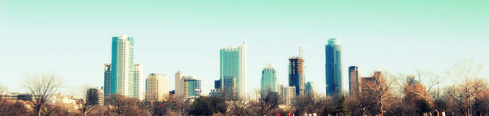 The city skyline of austin, texas on a windy day. people in the park flying a kite in the blue sky.