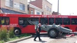 A Port Authority bus that hopped a curb and crashed into a war memorial cannon came to a rest against a wall Saturday, July 8, 2017, in the Brookline neighborhood of Pittsburgh. (AP)