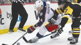 Photo by AP. Columbus' Scott Harrington (left) beats Pittsburgh's Bryan Rust to a loose puck during the second period of Wednesday night's game.