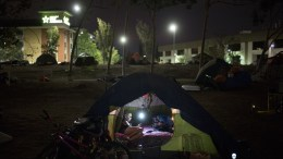 """Homeless Jacqueline Anderson, 63, passes time playing with her smartphone in a homeless encampment on the Santa Ana River trail Sunday, Dec. 10, 2017, in Anaheim, Calif. """"I like it here,"""" said Anderson who had been to a few other encampments before settling on the river trail. """"People always bring you food."""" (AP Photo/Jae C. Hong)"""