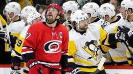 Carolina Hurricanes' Justin Faulk (27) looks at the scoreboard as Pittsburgh Penguins' Phil Kessel (81) is congratulated following Kessel's goal during the second period of an NHL hockey game in Raleigh, N.C., Friday, Feb. 23, 2018. (AP)