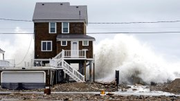 A house continues to get pummeled by high surf, Tuesday, March 6, 2018, as waves continue to breach the seawall in Marshfield, Mass. (AP)