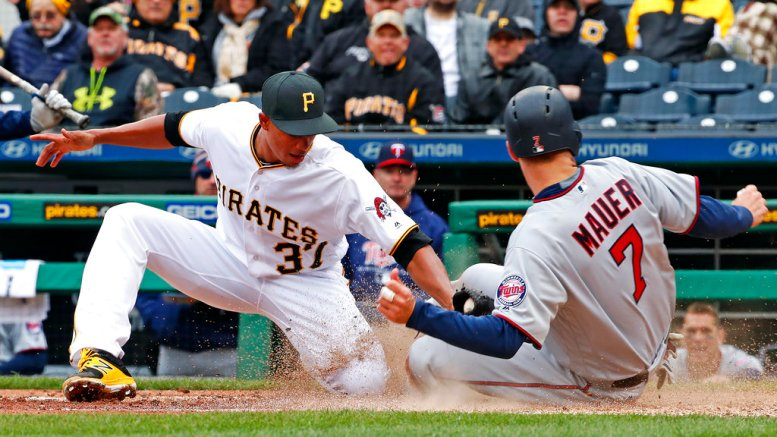 Minnesota Twins' Joe Mauer (7) scores on wild pitch ahead of the tag by Pittsburgh Pirates' Edgar Santana (37) during the sixth inning of the Pirates' home opener baseball game in Pittsburgh, Monday, April 2, 2018. (AP)