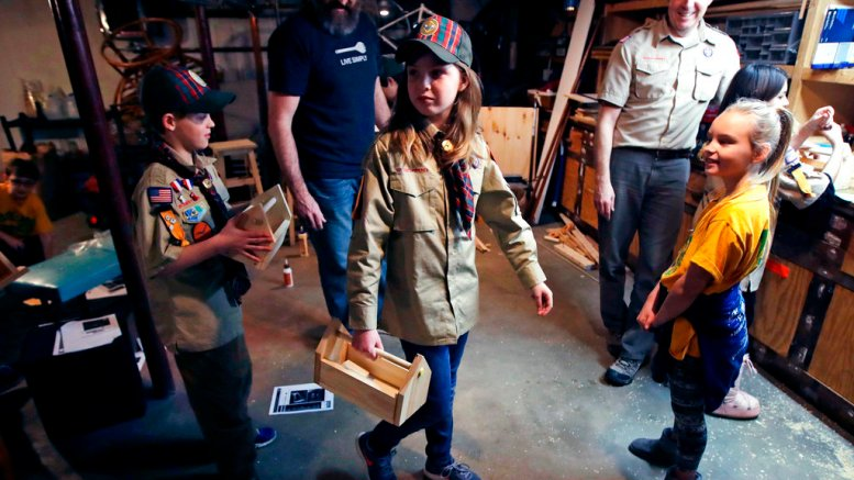 In this March 1, 2018, file photo, Tatum Weir (center) carries a tool box she built as her twin brother Ian (left) follows after a Cub Scout meeting in Madbury, N.H. (AP)