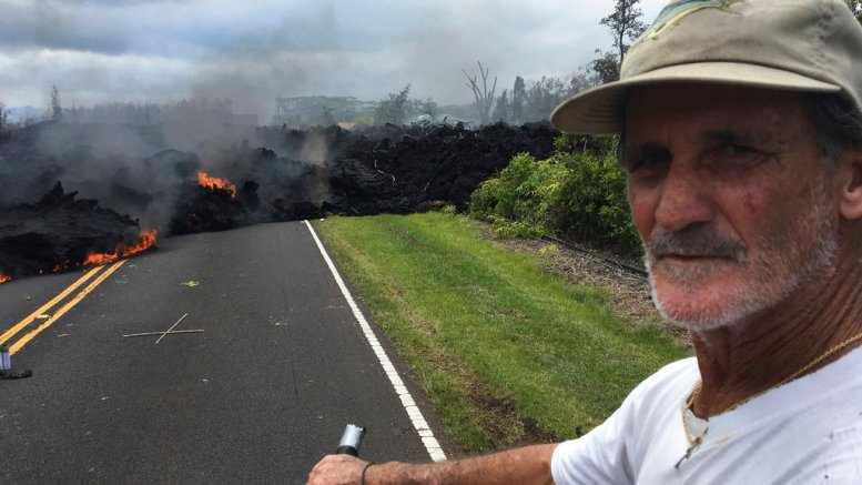Resident Sam Knox, 65, rides his bicycle to the edge of the road as lava burns across the road in the Leilani Estates in Pahoa, Hawaii, Saturday, May 5, 2018. (AP)