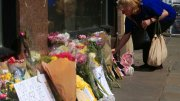 A woman leaves some flowers in Manchester, England, ahead of the Manchester Arena National Service of Commemoration at Manchester Cathedral to mark one year since the attack on Manchester Arena, Tuesday May 22, 2018. (AP)