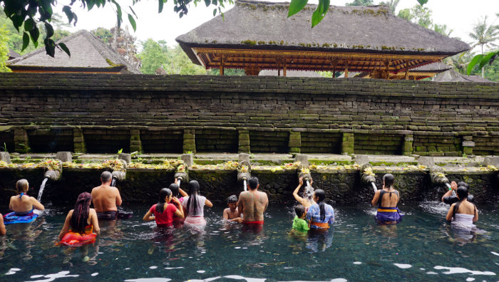 People lining up to bathe themselves under the water spouts at Tirta Empul water temple.