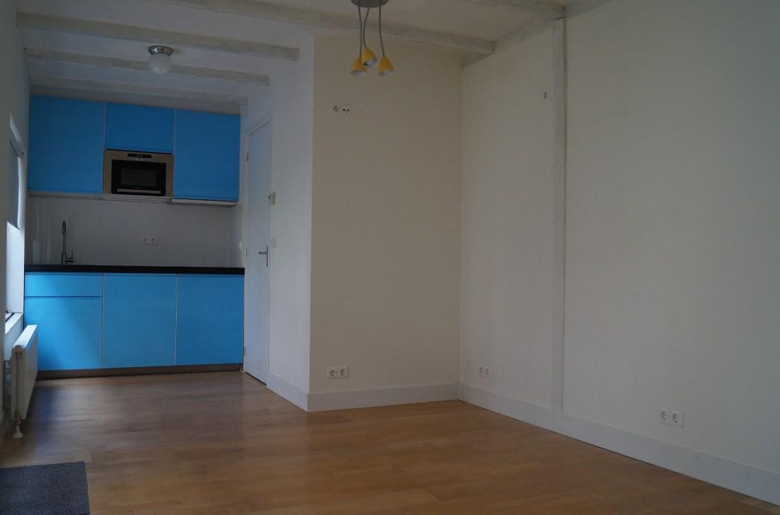 Een deel van de kamer met de open keuken
