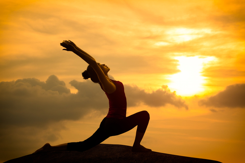 Young asian woman practicing yoga warrior pose at sunset