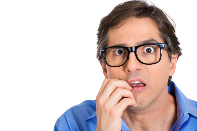 Closeup portrait nervous, stressed young nerdy guy, man with eye glasses biting fingernails looking anxiously craving something isolated white background. Negative emotion expression feeling, reaction
