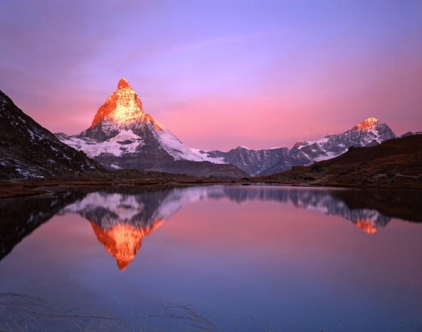 Mission Matterhorn, View from Riffellake to Matterhorn (left) Das Matterhorn (4478m) wird von den ersten Sonnenstrahlen beleuchtet, spiegelt sich im Riffelsee. Schweiz
