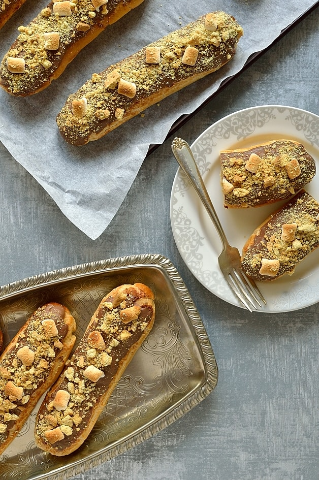 S'mores eclairs - crisp, craquelin topped choux pastry fingers with toasted marshmallow creme patissiere, chocolate, toasted mini marshmallows & biscuit crumbs