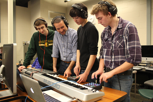 Jason Heath points to one of the gyroscopes student Michael Gershuny is composing with as his classmates Callum McLaughlan and Johnny Bear listen in.