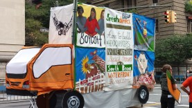 A float in the shape of a Fresh Direct Truck with various messages on them