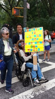 A woman in a wheelchair sporting glasses with peace sign shaped lenses holding a sign