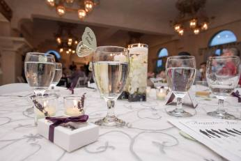 Butterfly placecards perched on wine glasses.