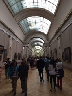 LONG hallway of paintings in the Louvre in Paris.