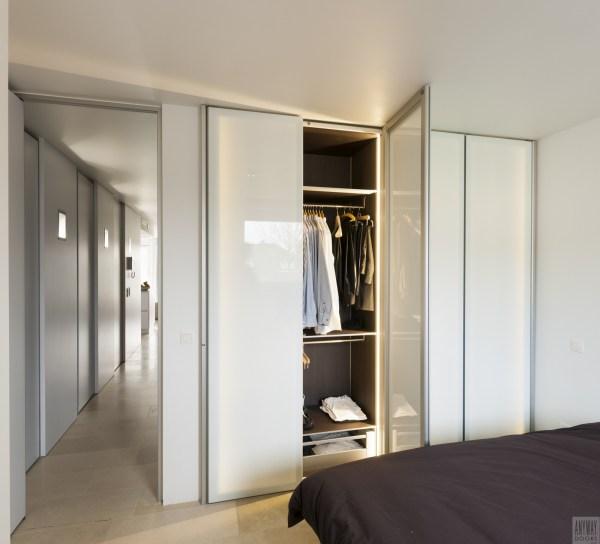 Garderobekasten op maat met witte glazen deuren.