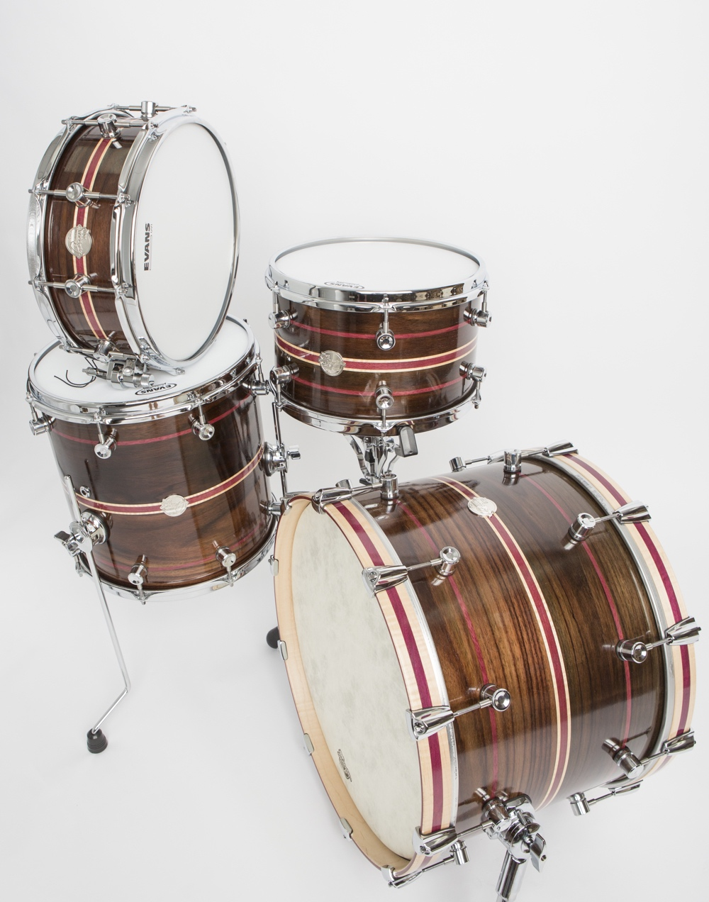 "Doc Sweeney's Panther Kit inlay (comprising a 20"" x 14"" bass drum; 14"" x 14"" and 13"" x 8"" mounted toms; and 14"" x 5.5"" snare drum) is made of steam-bent East Indian rosewood with purpleheart and maple inlays. It also features curly maple hoops with purpleheart. Have you ever seen another complete kit made of solid rosewood?"