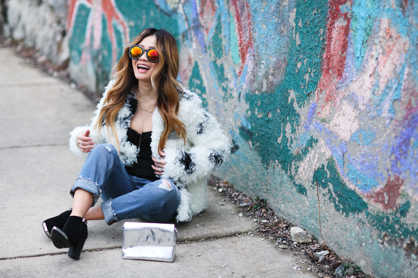 corset top and curly faux fur coat with reflective sunglasses and ripped jeans