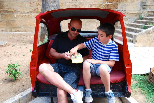 Stefano and Luca sample local pastries in the back end of a Fiat 500-turned street art.