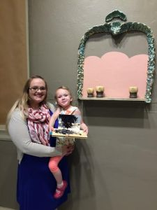 Lauren Taylor and her daughter Eleanor Farris pose with their respective pieces that are on display at the Reece Museum. (Photograph by: Jordan Hensley)
