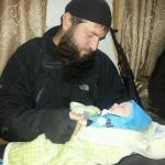 A fighter with a baby identified as Sayfullakhs son, after his death in Aleppo