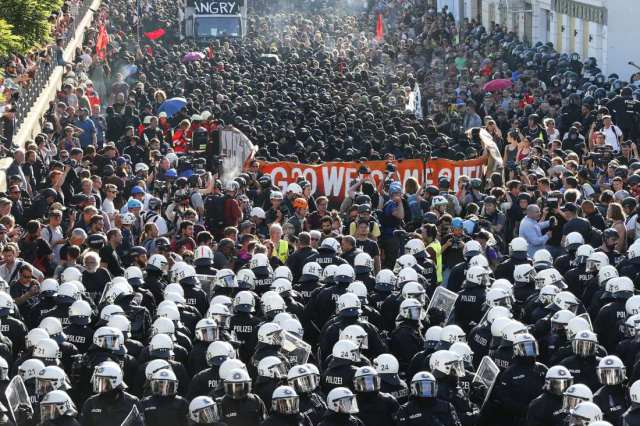 German riot police stand in front of protesters during the demonstrations during the G20 summit in Hamburg