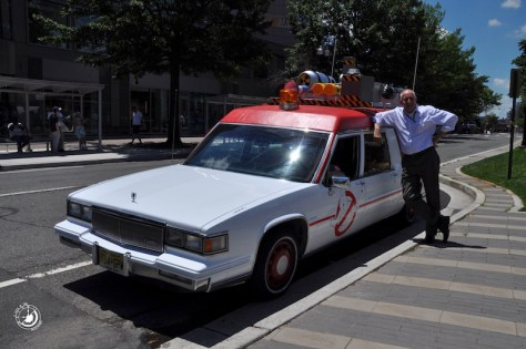"""A fan stands next to the new Ecto-1 from the upcoming film """"Ghostbusters"""" outside of the Clarendon Metro in Arlington, VA"""