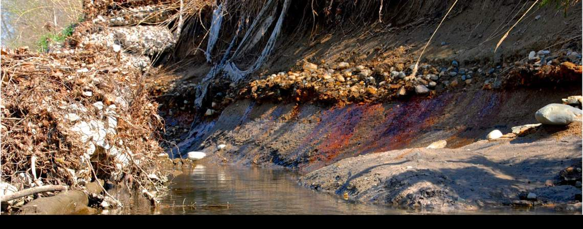 The river banks are eroding and the abutting coal ash pits leaching toxic waste into the surface and groundwater.  Photo by Pam Richart, Eco-Justice Collaborative. April 2016.