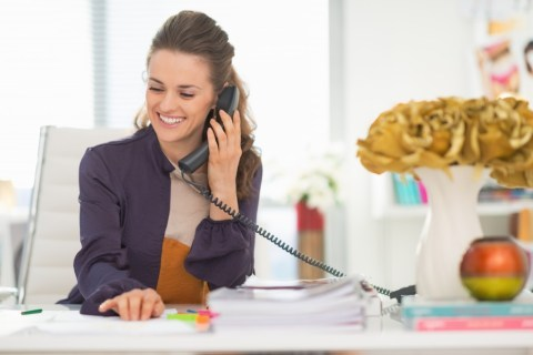 Happy woman talking phone in office