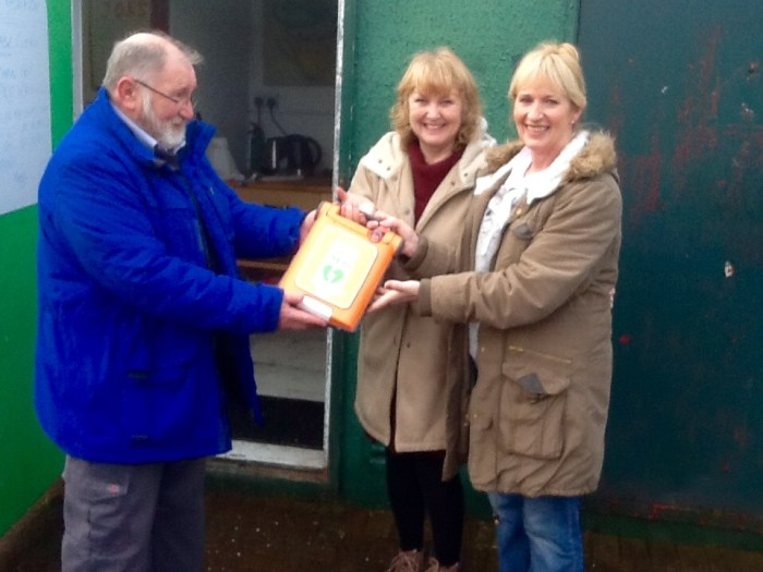 Allotments chairman Nigel being presented with defibrillator by Doreen and Peggy who organised the race night that raised the required funds.
