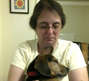 Small black and rust colored hound dog is sitting on a woman's lap with her head leaning up against her, eyes closed