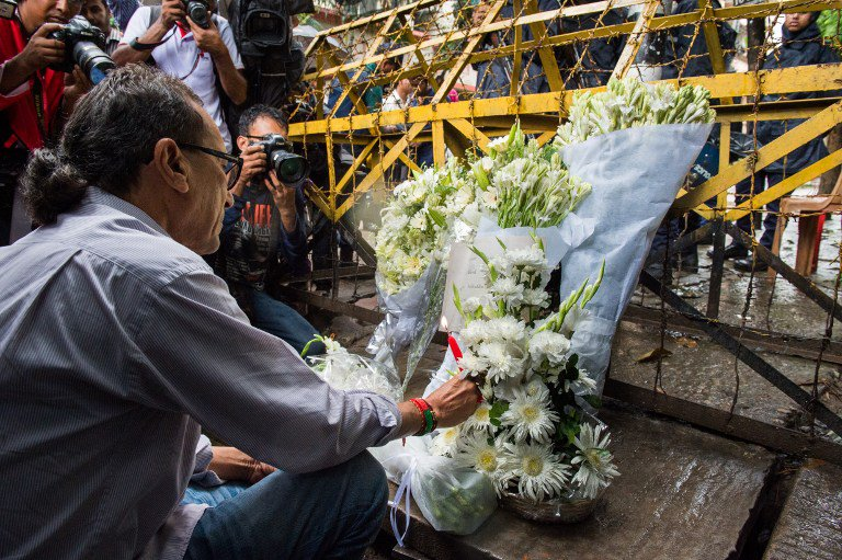 A Bangladeshi social activist lights a candle on floral arrangement that he placed on July 3, 2016 on a road block in Dhaka leading to an upscale cafe that was the site of a bloody siege. Bangladesh began observing two days of national mourning on July 3 after 20 hostages were slaughtered at a restaurant packed with foreigners in a terrifying escalation of a campaign of attacks by Islamist extremists. Seven Japanese and 9 Italian nationals were killed in the attack. / AFP PHOTO / ROBERTO SCHMIDT