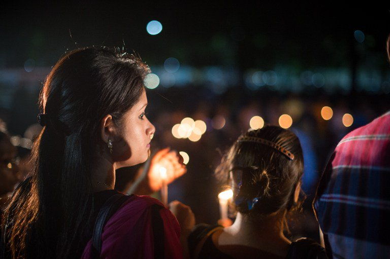 """A Bangladeshi woman holds a lit candle as she joins others to wish for peace during a candle-light vigil following an attack and seige in Dhaka on July 3, 2016. Bangladesh said July 3 the attackers who slaughtered 20 hostages at a restaurant were well-educated followers of a homegrown militant outfit who found extremism """"fashionable"""", denying links to the Islamic State group. As the country held services to mourn the victims of the siege in Dhaka, details emerged of how the attackers spared the lives of Muslims while herding foreigners to their deaths. / AFP PHOTO / ROBERTO SCHMIDT"""