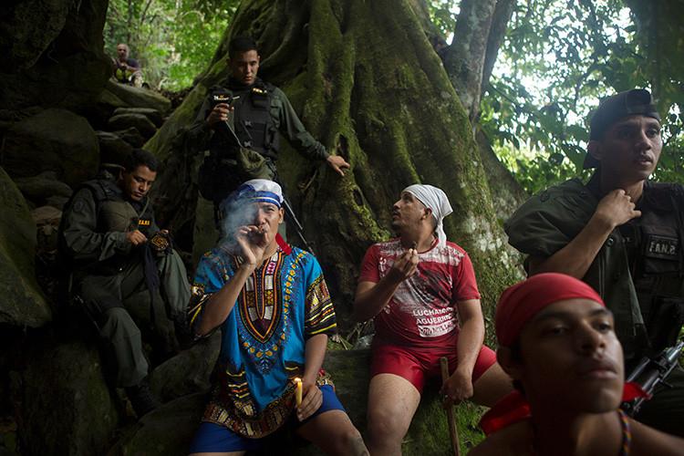 Creyentes fuman cigarros junto a la Guardia Nacional de Venezuela en el santuario de María Lionza , Venezuela 11 de octubre de 2015. REUTERS / Marco Bello