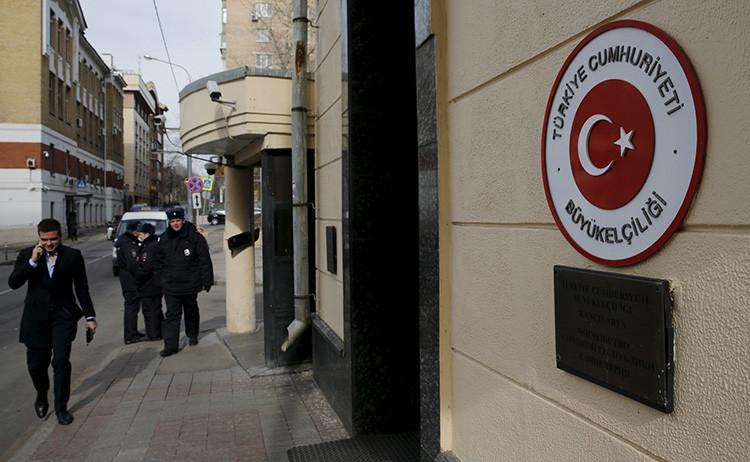 Un hombre pasa delante de agentes policiales que hacen guardia junto a la Embajada de Turquía en Moscú.