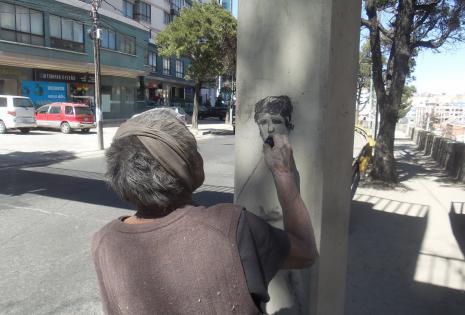 Un artista callejero dibuja el rostro de Donald Trump.