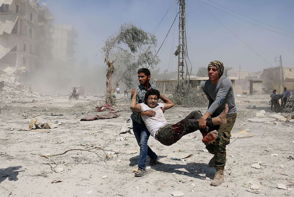 EDITORS NOTE: Graphic content / Syrian civilians carry a wounded man in the Maadi district of eastern Aleppo after regime aircrafts reportedly dropped explosive-packed barrel bombs on August 27, 2016. At least 15 civilians were reported killed when two bombs fell several minutes apart, near a tent where people were receiving condolences for those killed this week. / AFP / AMEER ALHALBI (Photo credit should read AMEER ALHALBI/AFP/Getty Images)