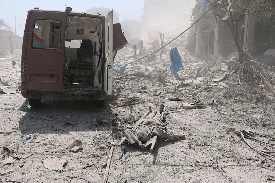 EDITORS NOTE: Graphic content / A corpse lies behind a damaged ambulance in the Maadi district of eastern Aleppo after regime aircrafts reportedly dropped explosive-packed barrel bombs on August 27, 2016. At least 15 civilians were reported killed when two bombs fell several minutes apart, near a tent where people were receiving condolences for those killed this week. / AFP / AMEER ALHALBI (Photo credit should read AMEER ALHALBI/AFP/Getty Images)
