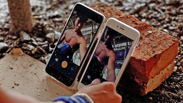 Shi Shenwei, usa sus teléfonos para grabar su rutina de barra fija, en donde se construye un templo budista en el pueblo de Huangshan, cerca de Quanzhou, provincia de Fujian, China