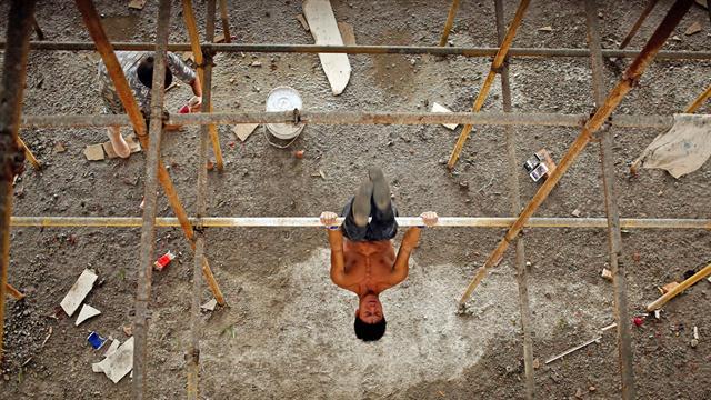 Shi Shenwei, realiza una rutina de barra fija, en un andamio de la obra en construcción de un templo budista,en el pueblo de Huangshan, cerca de Quanzhou, provincia de Fujian, China